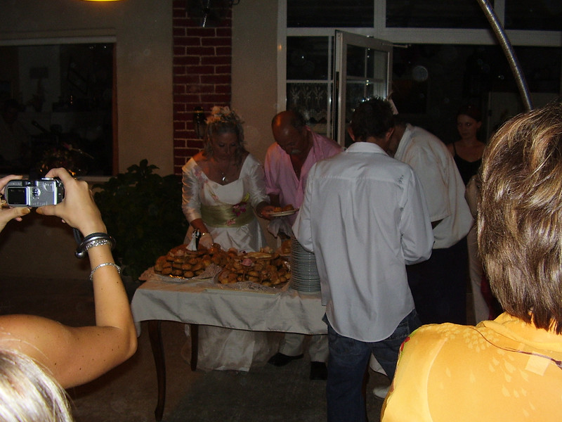 Daniel and Muriel serving the traditional wedding pasty (similar to a doughnut covered with honey) to guests.
