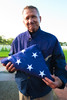 Bob Thompson embraces the U.S. Flag, remembering his role in WWII.