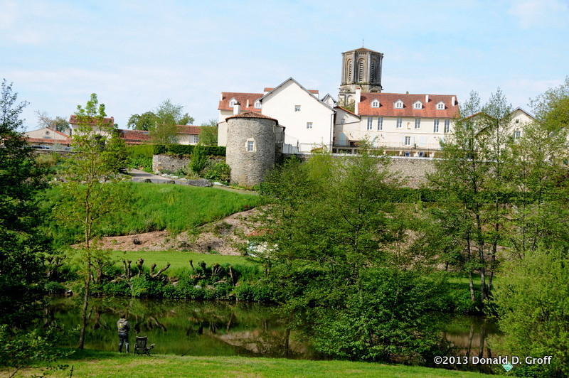 river on edge of Vouvant, below a remaining section of the city wall.