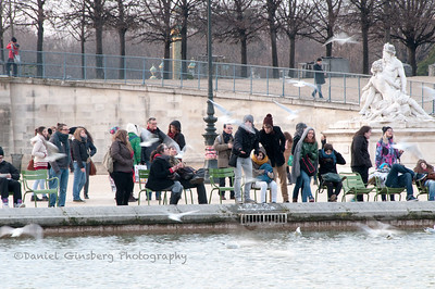 People sitting around a lake in Jardin des Tuileries.