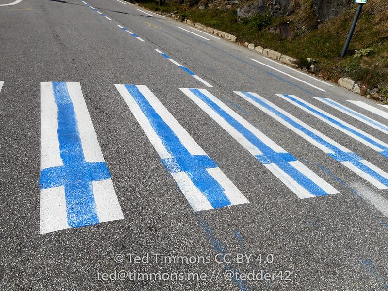 Finnish flag painted onto crosswalk bars.