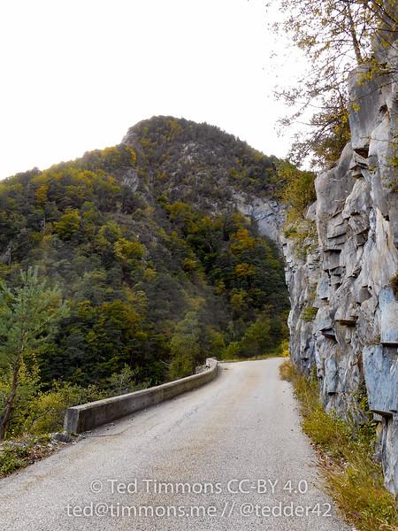 Rock wall, narrow road.