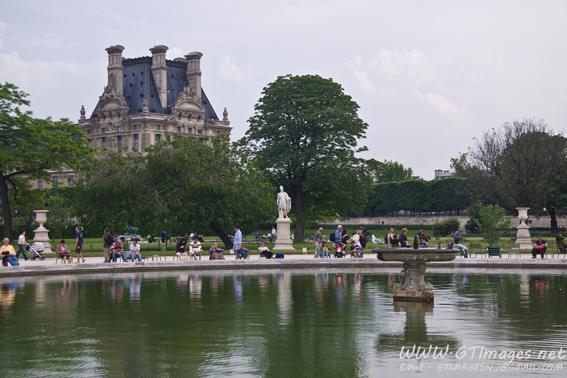Paris - the many parks are filled with people, and artwork. The surrounding buildings also add to the atmosphere.