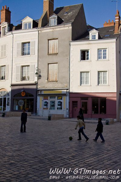 Orleans France - Children playing  a game of soccer in a square.