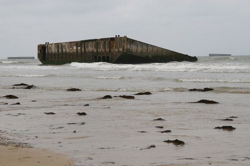 The concrete caissons lying on the beach at Arromanches which are the remains of the British Mulberry Harbour.