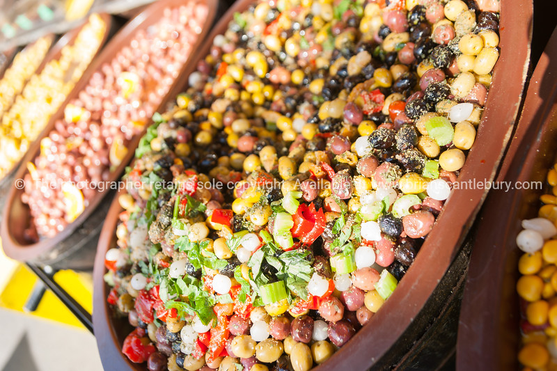 Antipasto pickled olives and food in market bowls, Colombiers, France.