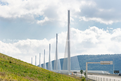 Millau Bridge piers disappear between distant hills across valley and green grassy slope, France.