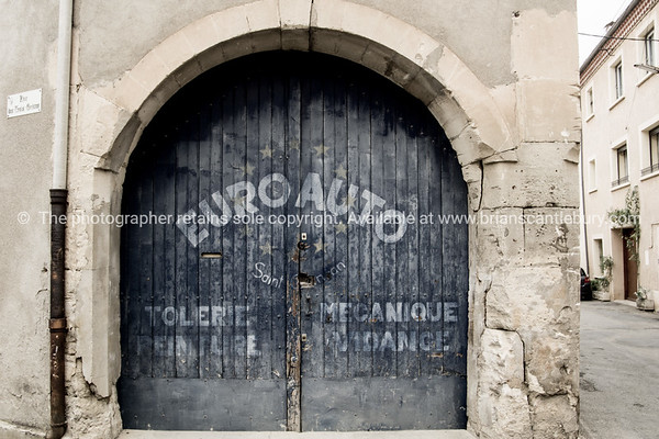 Old garage door blue with faded sign-writing in back street Saint Chinian, France