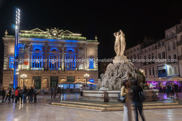 Night in the Place de la Comédie wonderful architecture Three Graces fountain and Opera House on  promenade under night lights and long exposure Place de la Comédie Montpellier France urban & architectural