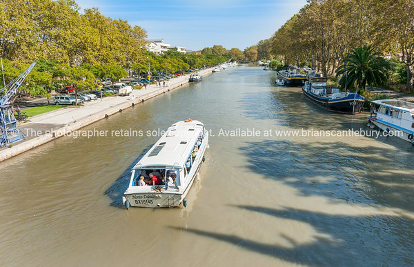 River boats moored along Canal Du Midi as  Monto Dabalo with tourist passengers passes along after crossing Orb Aqueduct in Beziers, France