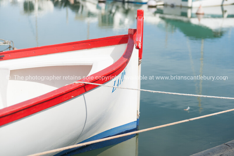 Bold red, white blue closeup of aft of Mediterraneanfishermans boat moored at Colombiers