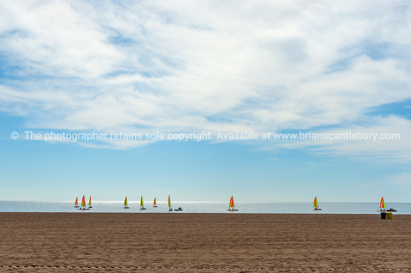 Wide sandy Mediterranean beach with fleet of small yachts with bright sails just off shore in learn to sail lessons.