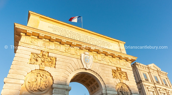 French flag flutters against setting blue sky as low sun casts golden hue on Arch of Triumph at entrance or Porte du Peyrou is a triumphal arch in Montpellier, It is situated at the eastern end of the Jardin de Peyrou, a park near the center of the city.