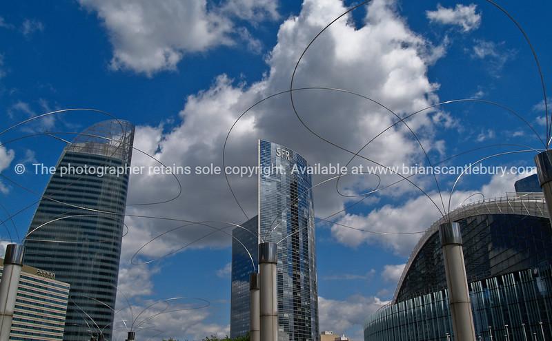 """Modern office building skyline, viewed through the twirls of a modern sculpture. Paris, France. SEE ALSO:   <a href=""""http://www.blurb.com/b/893039-paris-international-city"""">http://www.blurb.com/b/893039-paris-international-city</a>"""