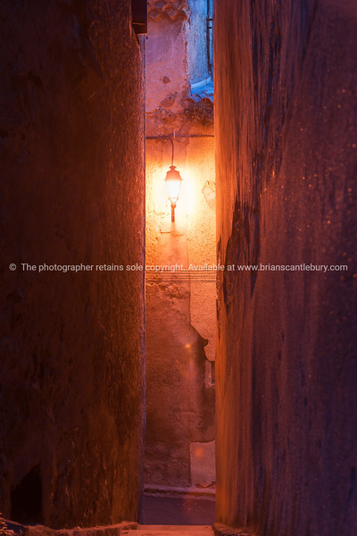 Warm glow of single street light at end of small Frech town narrow street between high walls of traditional architecture