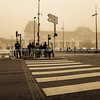 Toulouse street scene people waiting for signal to cross on pedestrian crossing in low light of cool misty morning.