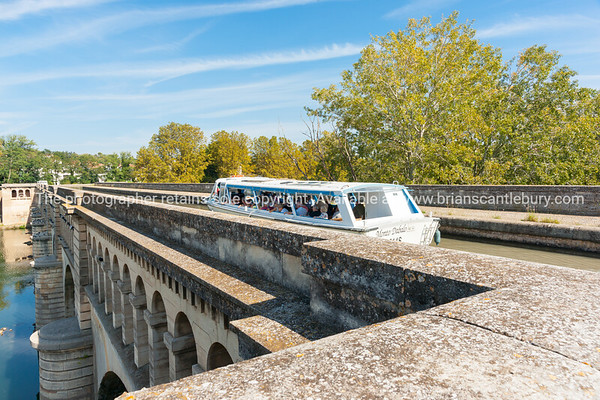 Tourist canal boat Monto Dabalo on Canal Du Midi crosses Orb River by aqueduct in Beziers, France