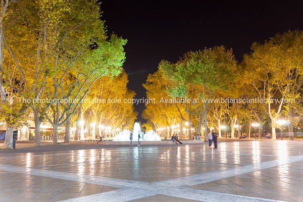 Fountain and tree lined promenade under night lights and long exposure at one end Place de la Comédie Montpellier France