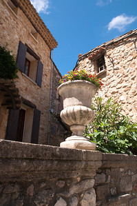 Flower pedestal on stone wall.