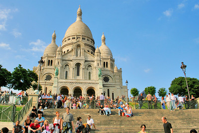 Lots of people listening to a band playing on the upper steps. Sacré Coeur (Sacred Heart) is situated in Montmartre. Montmartre was a little village on the outskirts of the city of Paris until it was discovered by artists in the nineteenth century.