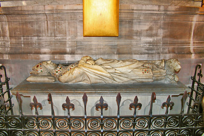Tomb of Simon Matiffas de Buci, who died in 1304. This is a recumbent figure in full costume, with a jewelled mitre, collar, necklace, etc., and a lion sleeping at the feet, in characteristic Gothic style,