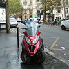 This motor bike with two front wheels is very common in Paris.