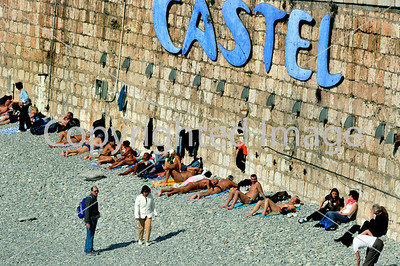 Nice, France - Beach Scene, Older French People Sunbathing on Castel Beach, near Mediteranean Sea, Lined up along Sea Wall.