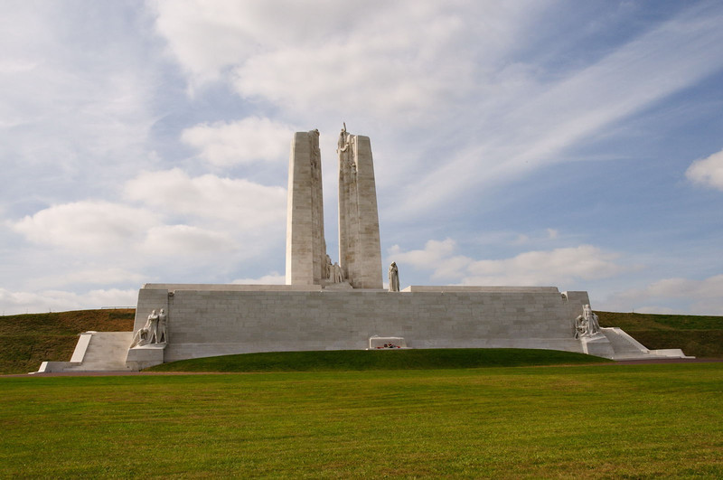 "<div style=""text-align: left;"">The memorial from the front. The two pylons stand 120 feet (30 metres) high from the base of the memorial. They represent Canada and France; one pylon has a carving of the maple leaf for Canada, the other plyon has the fleur-de-lis for France. Both countries shared the sorrow and sacrifice of war. <br><br> A stone sarcophagus is situated at the foot of the front wall of the memorial, which rises above it to 24 feet (7.3 metres). A Brodie steel helmet, as worn by the Canadian soldiers, a sword and laurel branches lie on the sarcophagus. <br><br> The Chorus: A group of eight figures high up on the top of the two pylons represent Justice, Peace, Hope, Charity, Honour, Faith, Truth and Knowledge. Peace is the highest figure on the monument, reaching upwards with a torch.</div>"