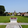 From the centre of the memorial grounds one can see, down a long avenue of trees, the rebuilt spires of Ypres.