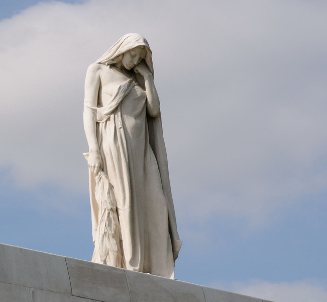 "<div style=""text-align: left;"">""Mother Canada"" or ""Canada Bereft"": A female figure draped in a cloak stands alone on the wall at the north-eastern side of the memorial. She bows her head and is looking down at a stone sarcophogus, representing Canada's war dead, at the base of the 24 foot (7.3 metres) wall below her. The magnificent view across the Douai plain and the location of the old enemy of the time spreads out before her. This figure is called Mother Canada or Canada Bereft, representing the nation of Canada mourning for her dead. The figure was carved from a single 30 tonne block of limestone.</div>"