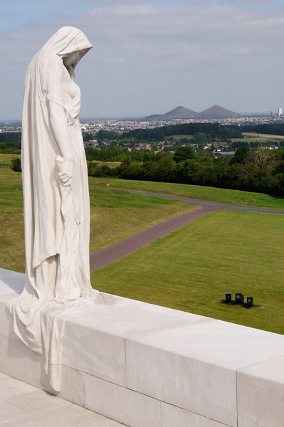 "<div style=""text-align: left;"">The mourning figure of ""Mother Canada"" on the Canadian National Vimy Memorial. She stands on the objective for the Canadian Corps, successfully won at the Battle of Vimy Ridge. Winning this high ground gave the Allies a view across the German rear areas on the Lens-Douai plain. The Double Crassier slag heaps at Loos-en-Gohelle can be seen on the horizon.</div>"