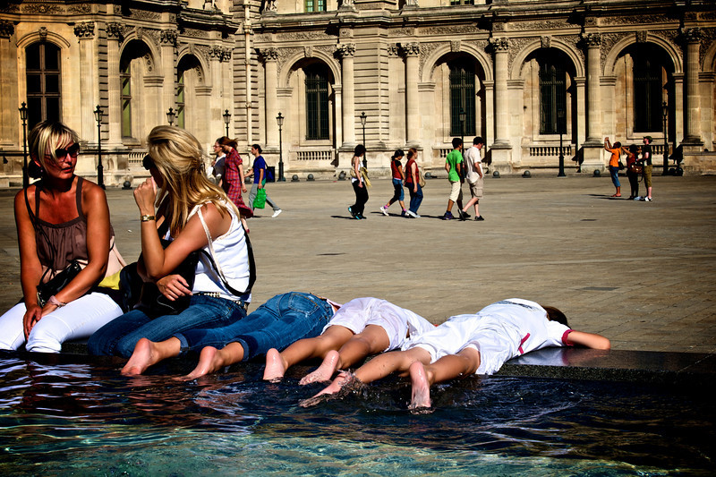 kids enjoying the pools in front of the Louvre.