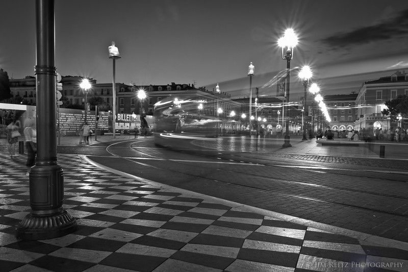 Nice's light rail train zooms past Place Messena at night.