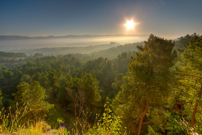 The sun rises over a misty Luberon Valley in Provence. View from the walking trail in Roussillon.