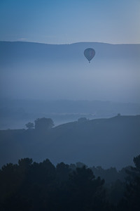 A hot-air balloon takes flight for an early morning cruise in the Luberon Valley.