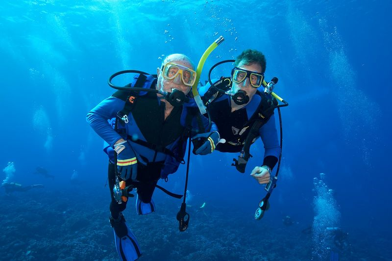 Grandfather and grandson, underwater: Ed Callan and Hal Tweto (Fakarava - South Pass)