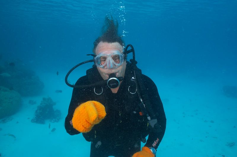 Guy de la Valdene points at the eel who is biting my safety sausage (Rangiroa - The Aquarium)