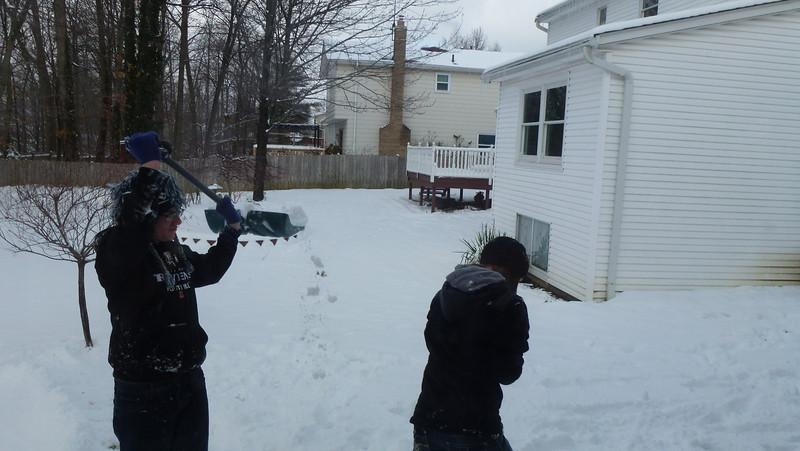 Jake shoveling snow on Julia.