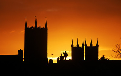 Guys working on a chimney, silhouetted against the Cathedral at sunset