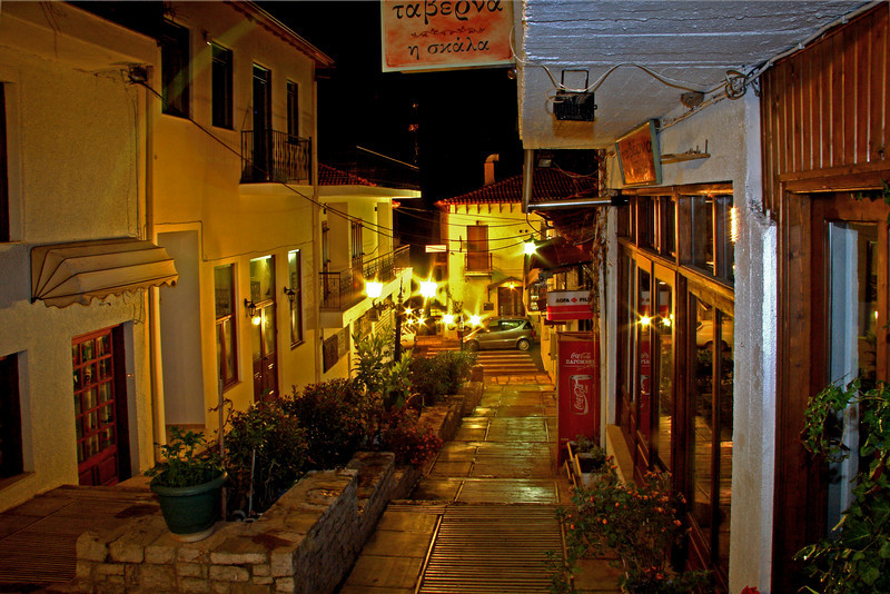 #574 Delphi Stores<br />  There are sidewalks connecting the streets in Delphi lined with various stores and gift shops lit up at night.