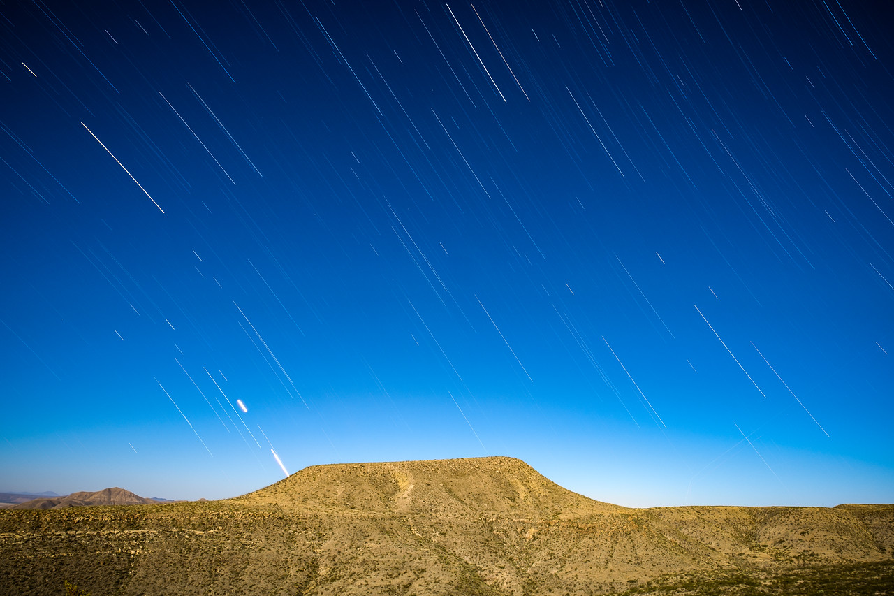 STAR TRAILS IN NEARLY DAYLIGHT CONDITIONS WITH THE SUPER MOON LIGHTING THE LANDSCAPE