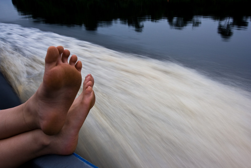Molly's feet on the side of the boat as we travel up the river Mpive.