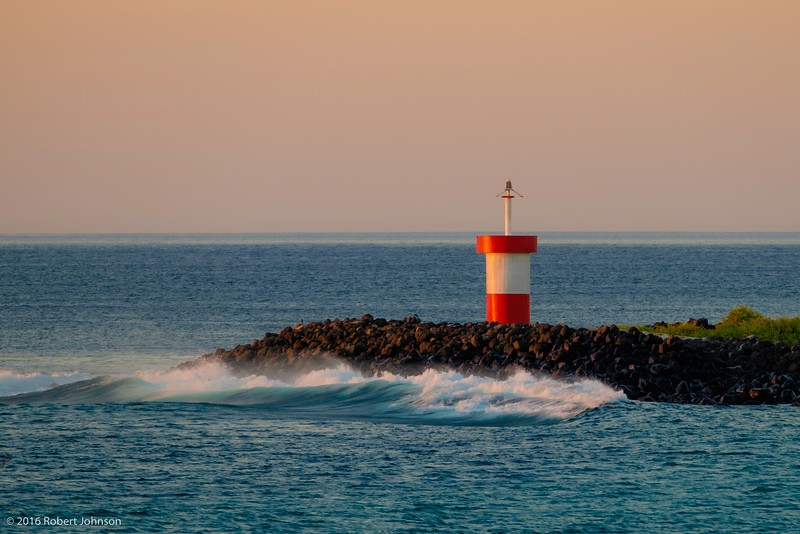Waves crashing at sunset near the lighthouse at Punta Carola, which is at the entrance to Puerto Baquerizo Moreno, Isla de San Cristóbal, Ecuador