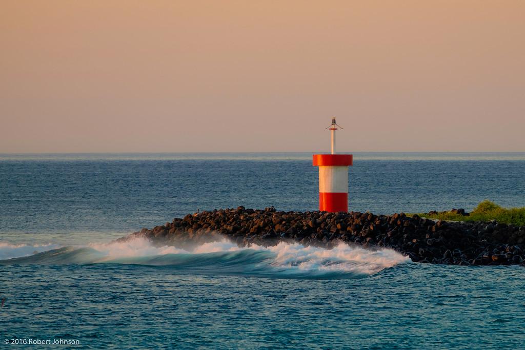 Waves crashing at sunset near the lighthouse at Punta Carola, which is at the entrance to Puerto Baquerizo Moreno, Isla de San Cristóbal, Ecuador