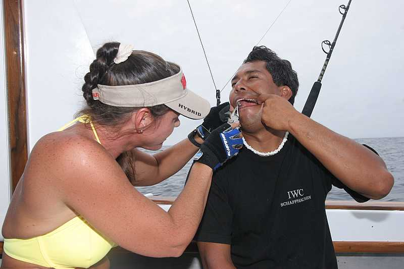 Tuesday, January 10, 2006<br /> <br /> Dr. Julie Ball finds time between catching fish to give a courtesy dental check up to our beloved mate Umberto Hernandez.  Luckily Tim had his Leatherman on hand to assist with the procedure.   Angela Vitale