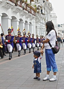 A Young Boy watches The Loyalty Day Parade that is held every Monday at the Capital Building in old Quito.  The soldiers are dressed in uniforms replicating those used by Napoleon's Army