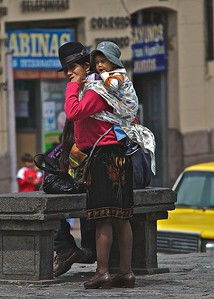 A lady in traditional dress and hat carries a small child in Quito, Ecuador