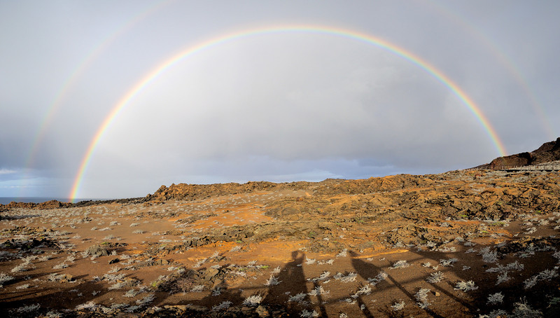 A double rainbow on Isla Bartolome's boardwalk to an overview of Pinnacle Rock.