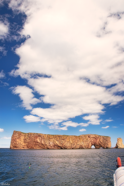 The famous Percé Rock. <br /> It appears from a distance like a ship under sail. It is one of the world's largest natural arches located in water and is considered a geologically and historically-rich natural icon of Quebec. The name is attributed to the pierced rock that formed an arch of 20 metres (66 ft) height on its seaward southern end, as though a needle had cut through the rock.