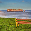 Let's sit here for a while.<br /> The famous Percé Rock. It appears from a distance like a ship under sail. It is one of the world's largest natural arches located in water and is considered a geologically and historically-rich natural icon of Quebec. The name is attributed to the pierced rock that formed an arch of 20 metres (66 ft) height on its seaward southern end, as though a needle had cut through the rock.